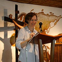 Kylie Cullen at a lectern with a cross behind her