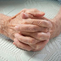 Elderly woman with hands clasped