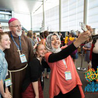 Bishop Oudeman smiles for a selfie with young people taking on the selfie challenge at ACYF15