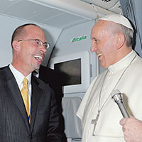 John L. Allen Jr laughs on board a flight with with Pope Francis